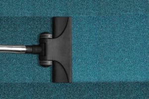 Carpet cleaning services - arial view of vacuum head on blue carpet