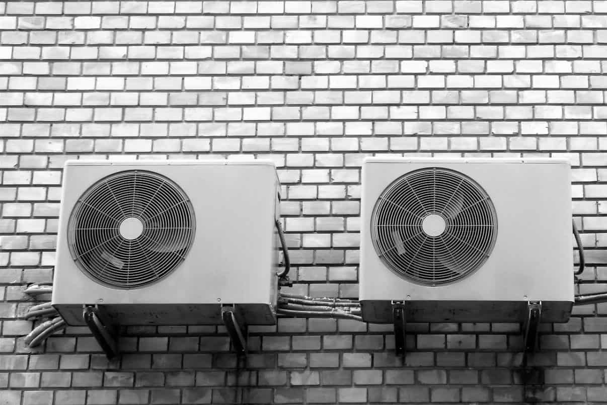 Black and white image of three air conditioners on a brick wall