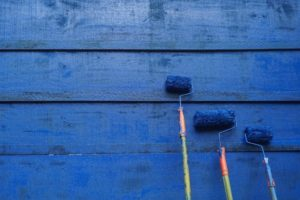 cerulean blue painted wooden wall with three paint rollers of descending height resting against it