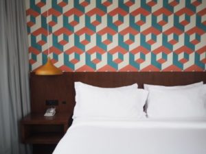 Blogpost 5 Projects You Really Shouldnt DIY - close-up of bed with geometric wallpaper background