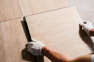 Gloved Hands Placing Floor Tile